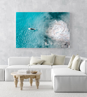 Aerial topdown of girl surfer in wetsuit paddling in blue water in a white fine art frame