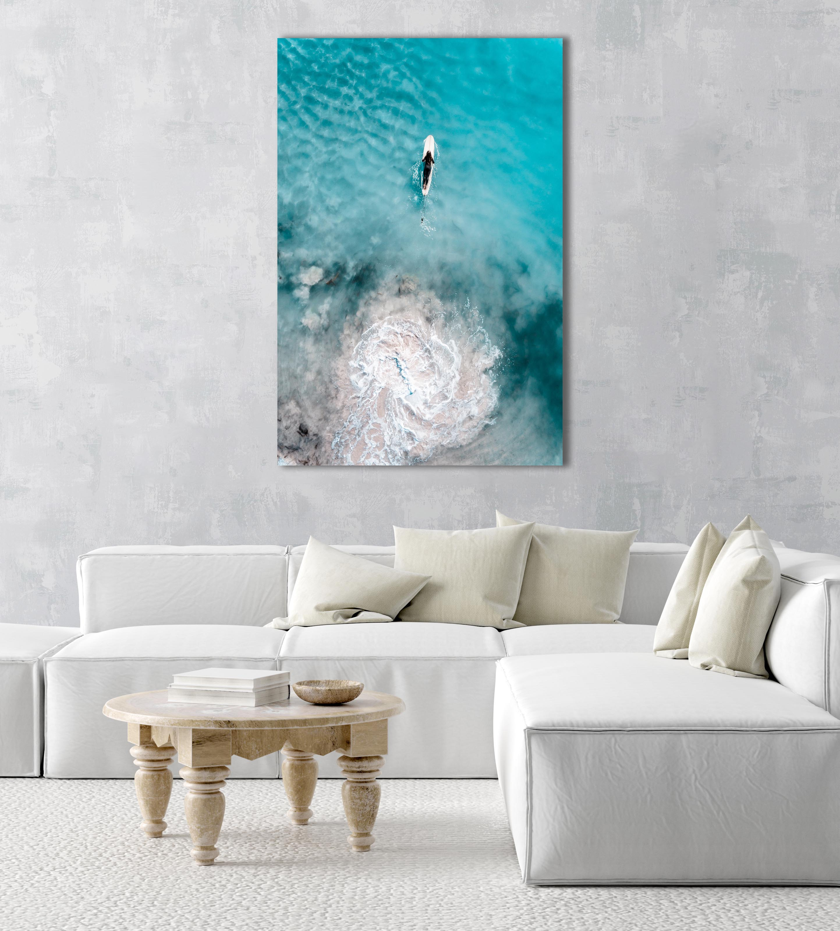 Aerial topdown of girl surfer in wetsuit paddling in blue water in a natural fine art frame
