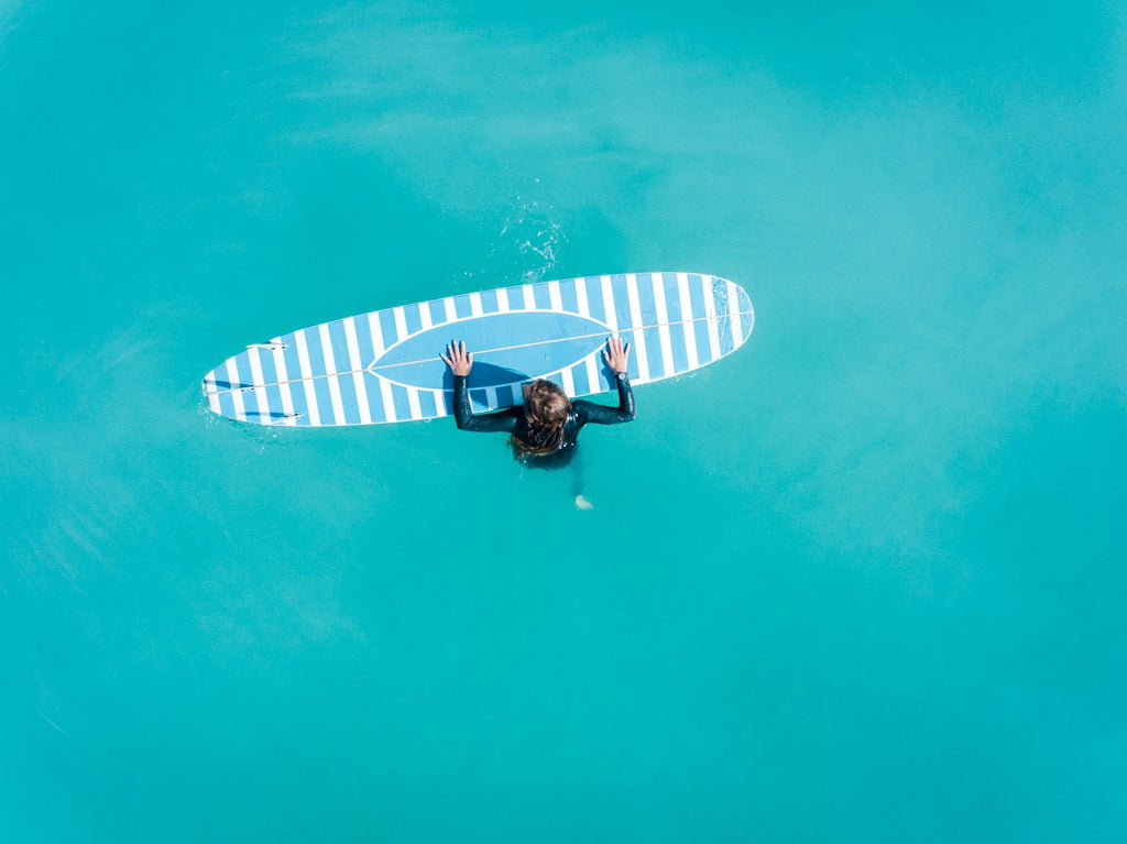 Aerial of girl holding striped surfboard in blue water in Camps Bay Beach