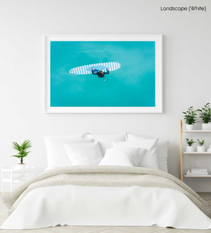 Aerial of girl holding striped surfboard in blue water in Camps Bay Beach in a white fine art frame