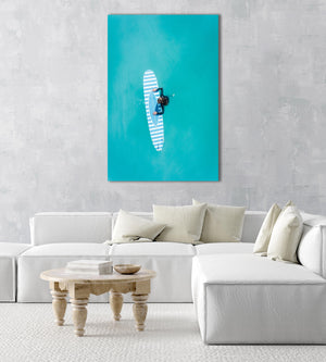 Aerial of girl holding striped surfboard in blue water in Camps Bay Beach in a natural fine art frame