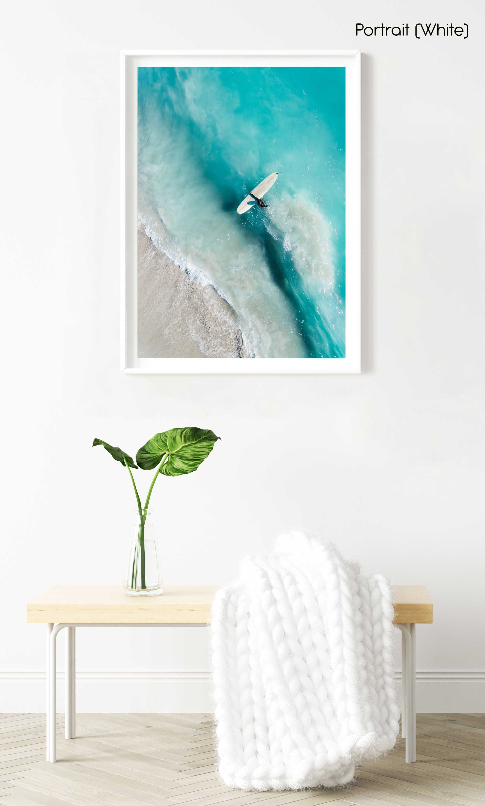 Girl walking back to shore with surfboard in blue water and waves in a white fine art frame