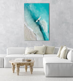 Girl walking back to shore with surfboard in blue water and waves in a natural fine art frame