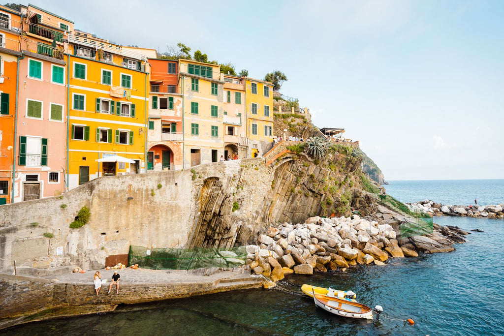 Man and woman sitting alongside docked boats and colorful buildings in Riomaggiore