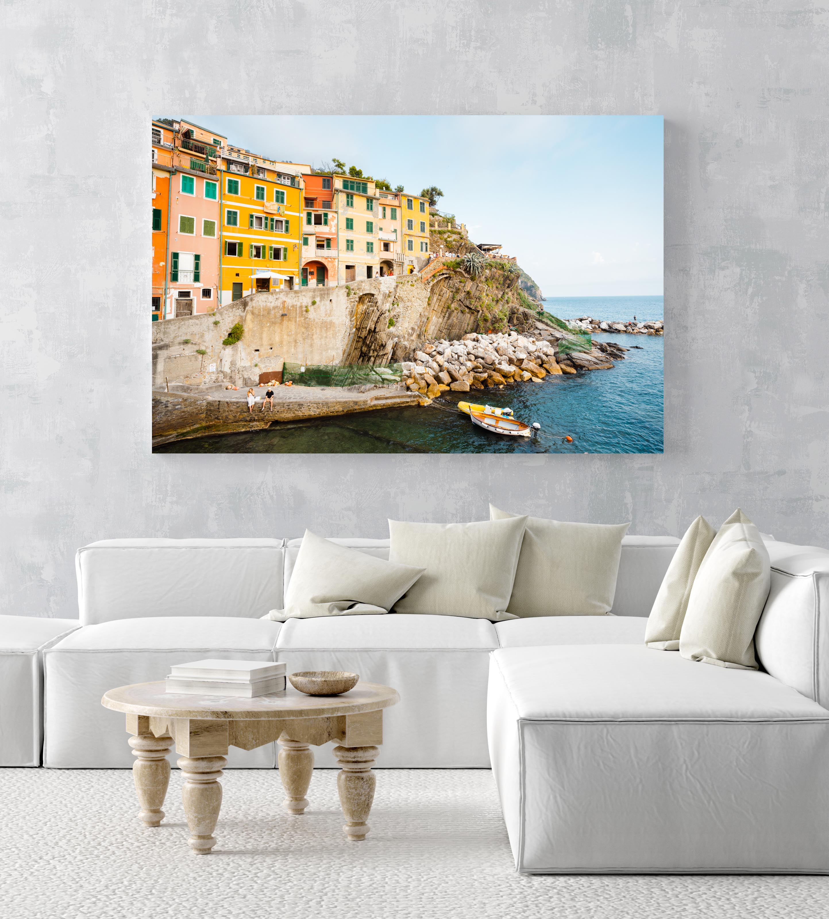 Man and woman sitting alongside docked boats and colorful buildings in Riomaggiore in an acrylic/perspex frame