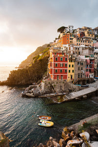 Docked boats and colorful buildings at sunset in Riomaggiore Cinque Terre
