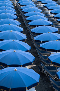 Blue umbrellas and beach chairs lined up in Italy