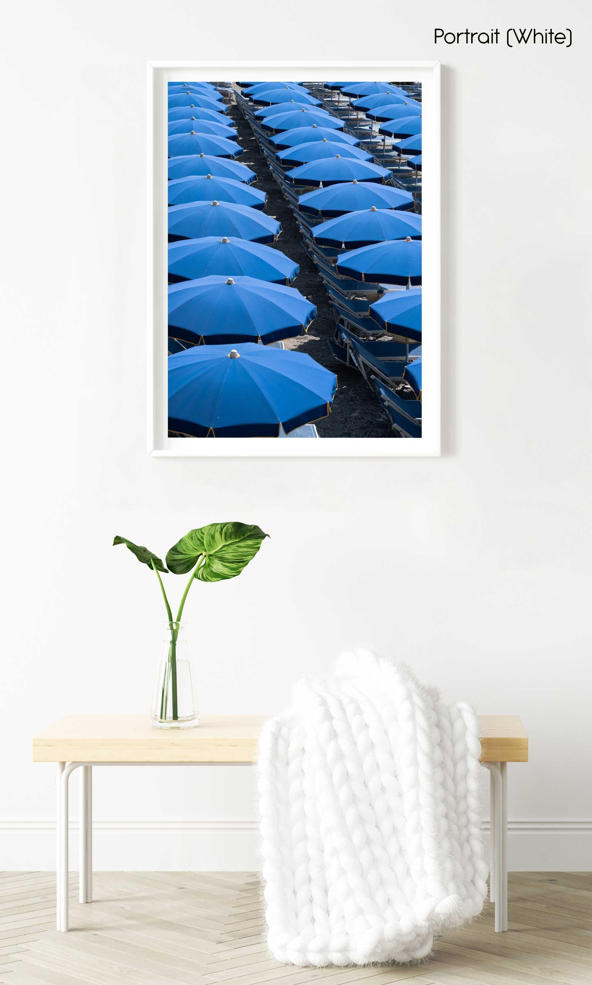 Blue umbrellas and beach chairs lined up in Italy in a white fine art frame