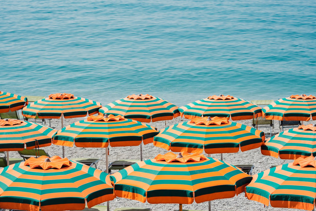 Rows of striped orange umbrellas and turquoise sea in Cinque Terre