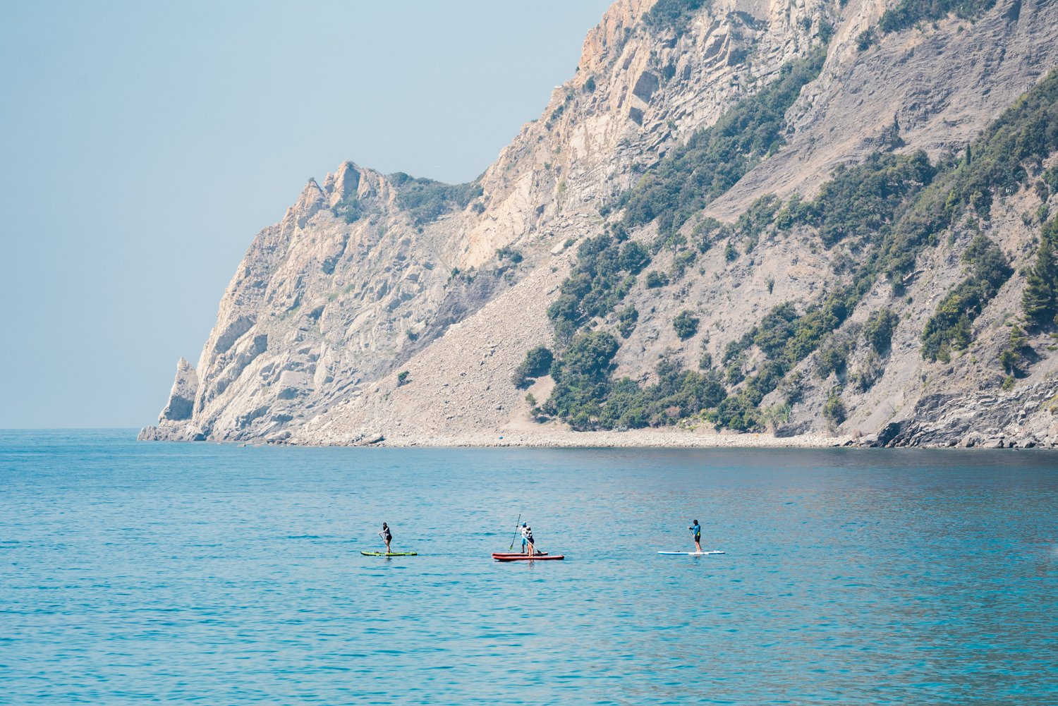 Four people paddling on board alongside mountains in Cinque Terre