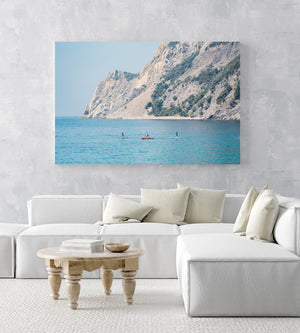 Four people paddling on board alongside mountains in Cinque Terre in an acrylic/perspex frame
