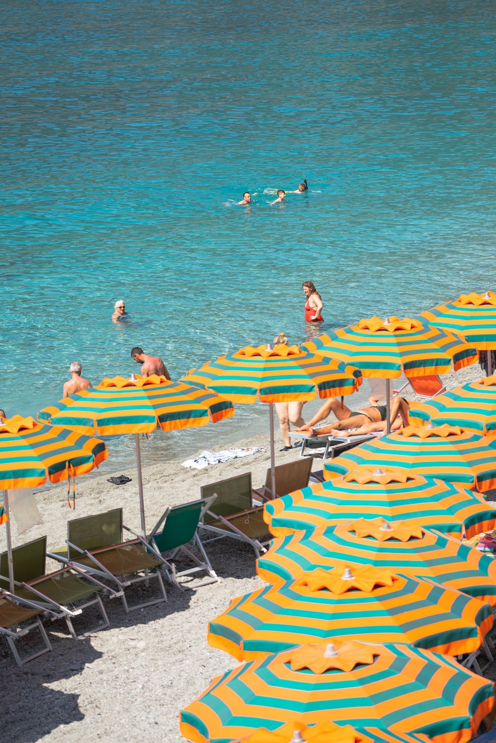 Orange umbrellas and people swimming in blue water on Monterosso beach