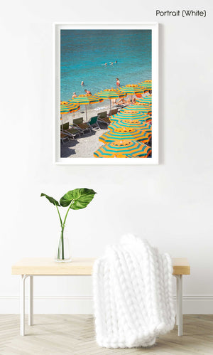 Orange umbrellas and people swimming in blue water on Monterosso beach in a white fine art frame