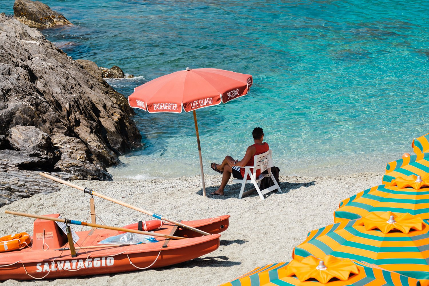 Italian lifeguard sitting under umbrella at blue water on Monterosso Beach