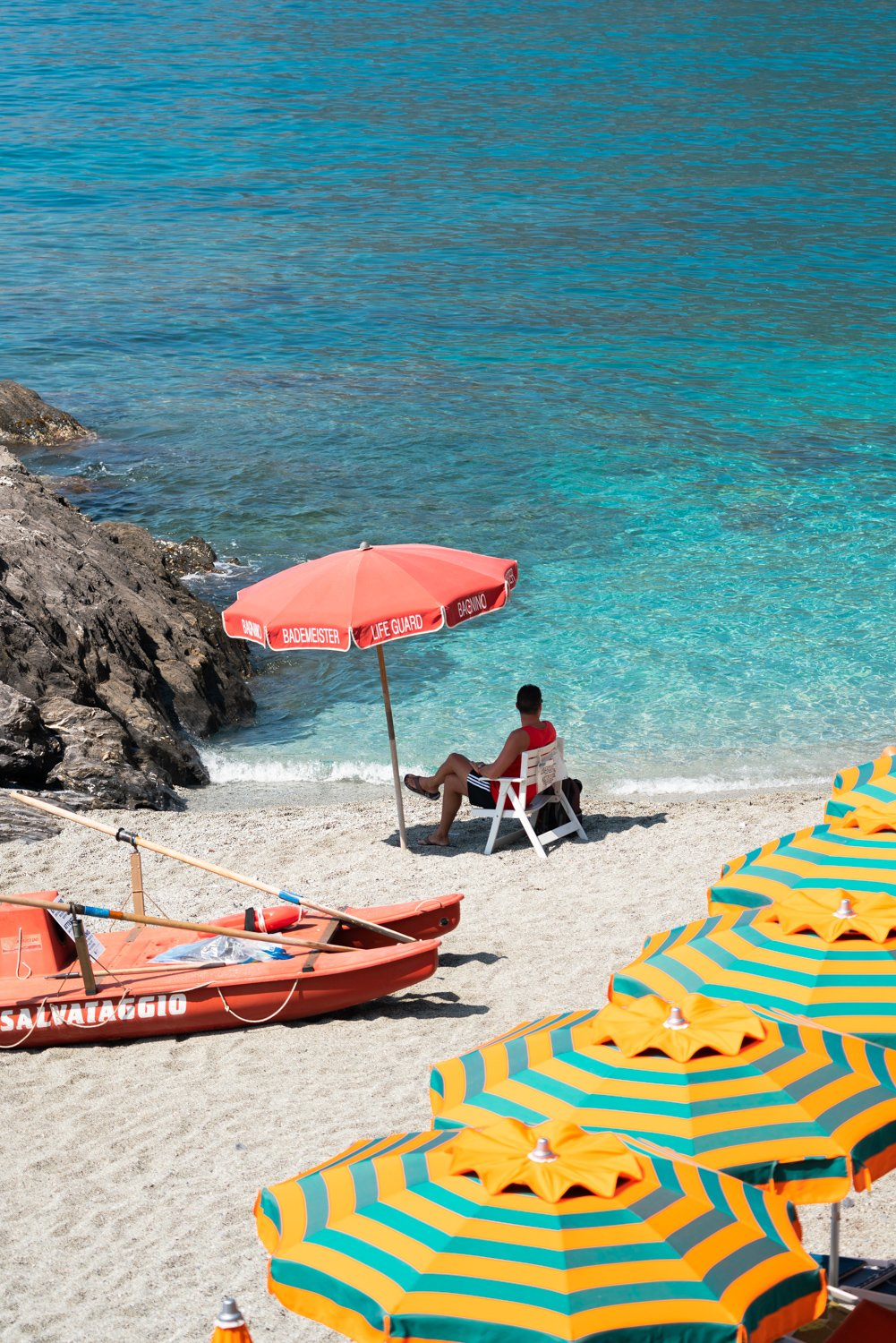Italian lifeguard sitting under umbrella with boat at blue water on Monterosso Beach