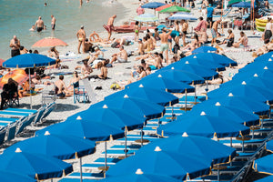 People lying on the sand next to blue umbrellas in Cinque Terre
