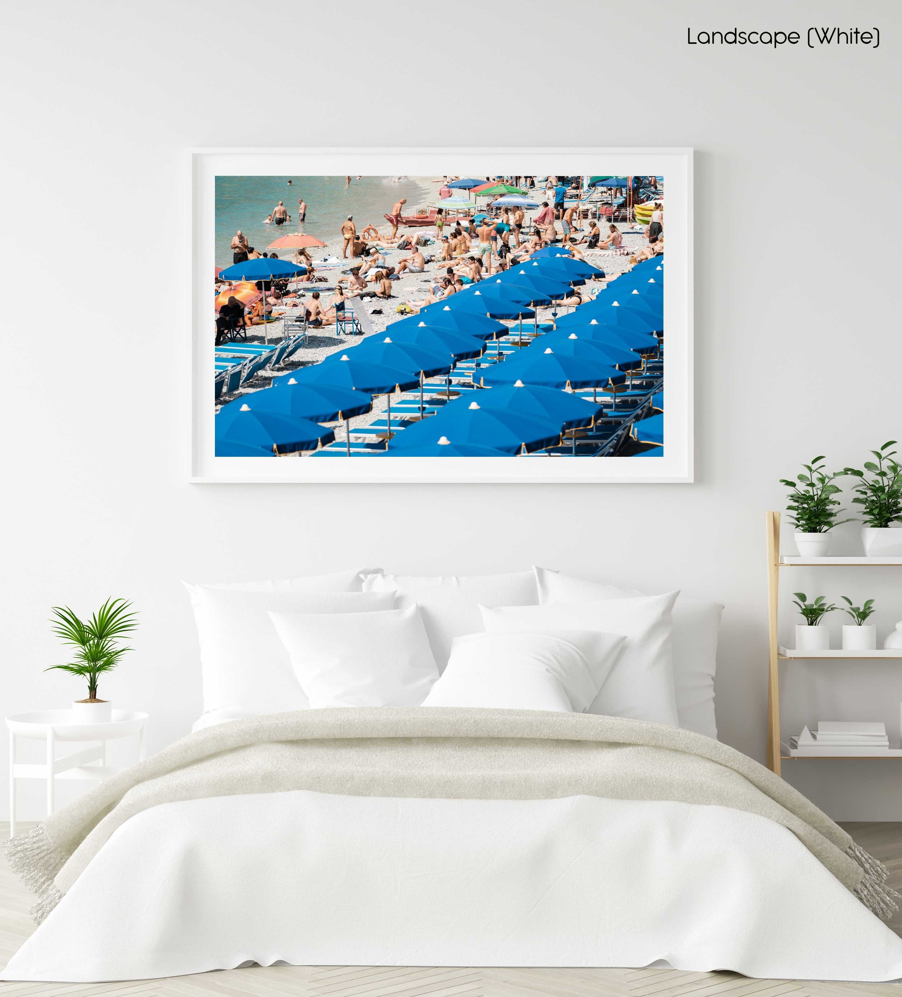 People lying on the sand next to blue umbrellas in Cinque Terre in a white fine art frame