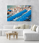 People lying on the sand next to blue umbrellas in Cinque Terre in an acrylic/perspex frame