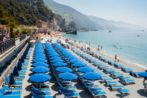 Rows of blue umbrellas along blue mediterranean sea in Cinque Terre