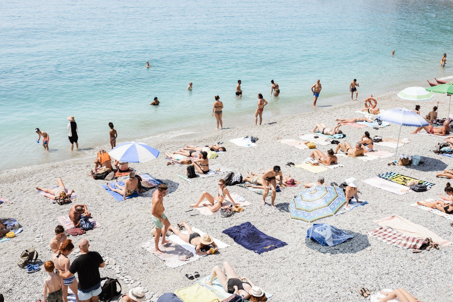 Beach goers lying on sand at italian beach