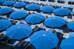 Woman lying under blue umbrellas seen from above