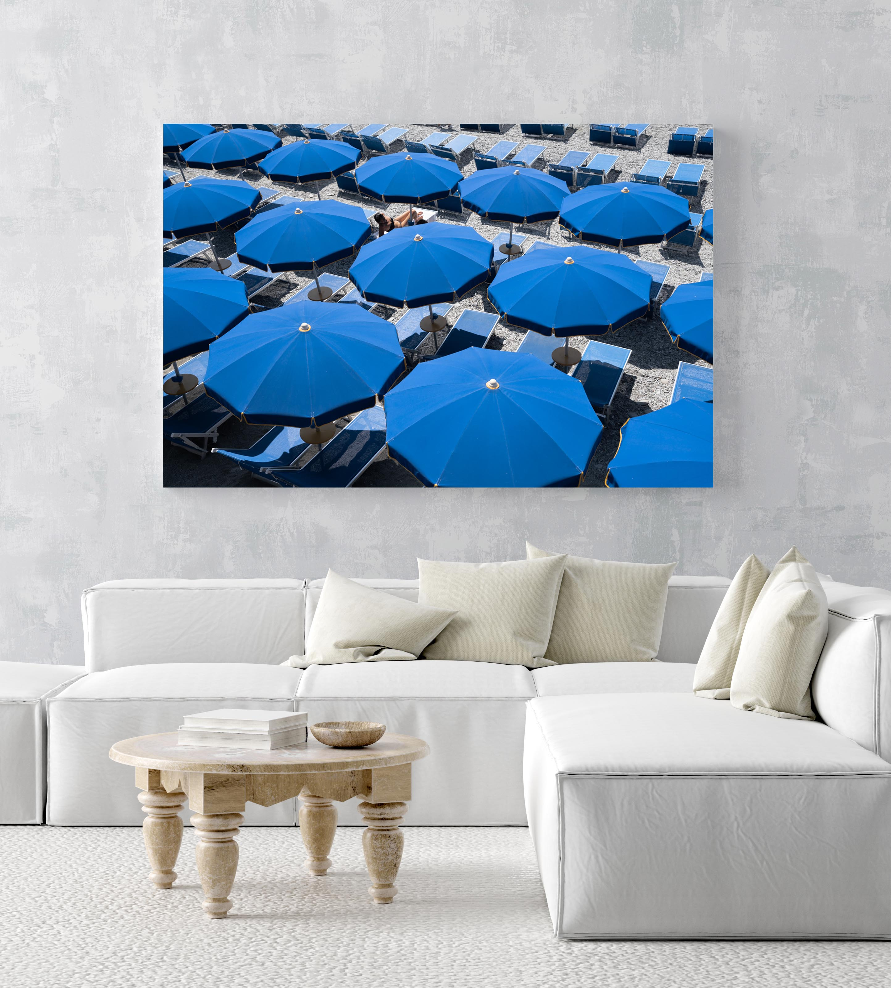 Woman lying under blue umbrellas seen from above in an acrylic/perspex frame