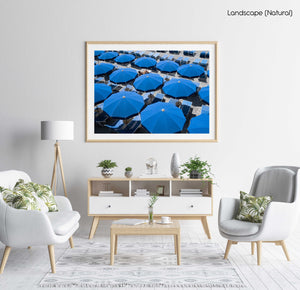Woman lying under blue umbrellas seen from above in a natural fine art frame