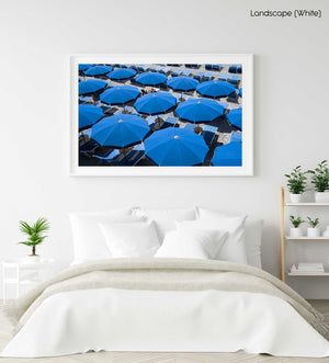 Woman lying under blue umbrellas seen from above in a white fine art frame