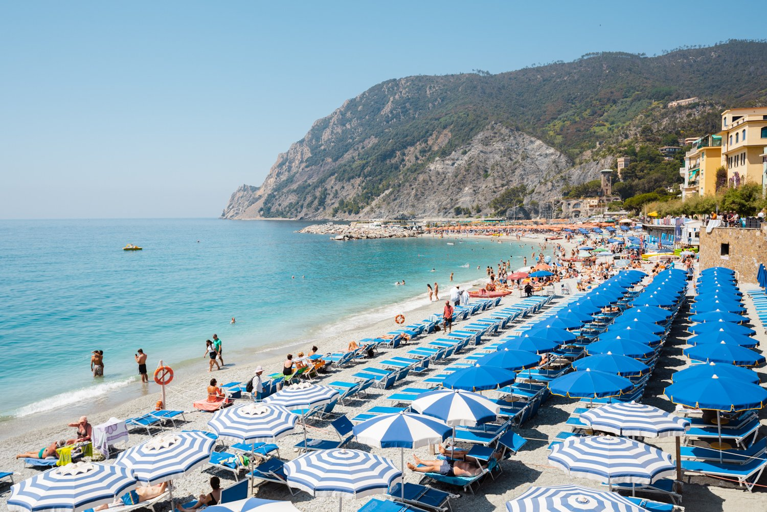 People and umbrellas at Monterosso beach Cinque Terre during summer