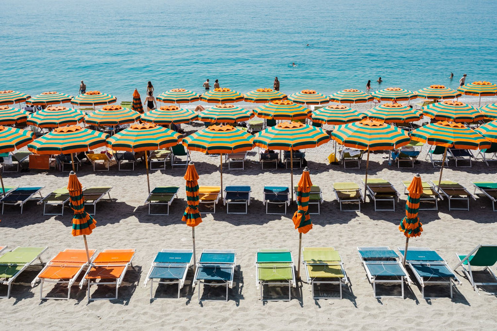 Orange, green and blue colors of umbrellas and sea in Cinque Terre