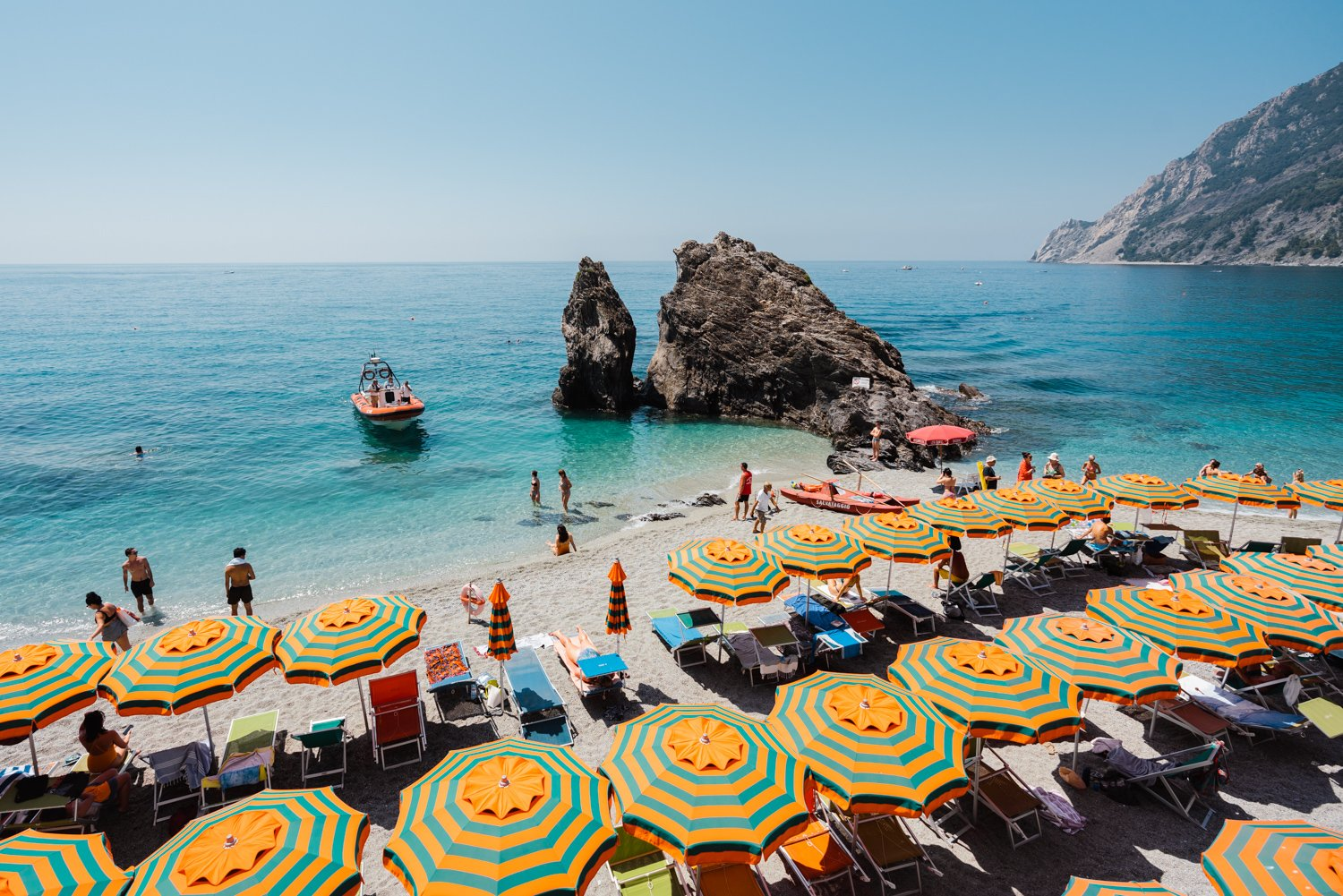 Orange striped umbrellas on beach in Italy with blue water and a boat arriving