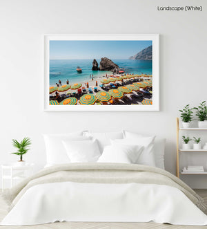 Orange striped umbrellas on beach in Italy with blue water and a boat arriving in a white fine art frame
