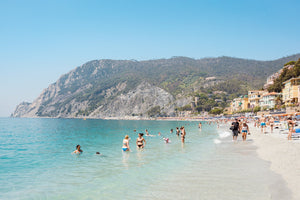 Hot sunny day with people swimming at Monterosso beach Italy