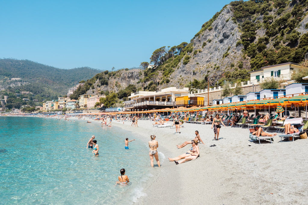 People swimming and sitting at colorful Monterosso beach in Cinque Terre