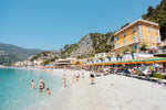 People swimming and sitting at colorful Monterosso beach in Italy