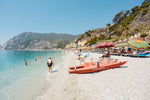 Italian vibes along Monterosso beach with people swimming and lying at water