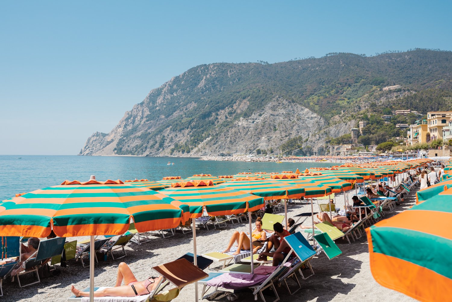Orange umbrellas and people tanning on Monterosso Beach Cinque Terre