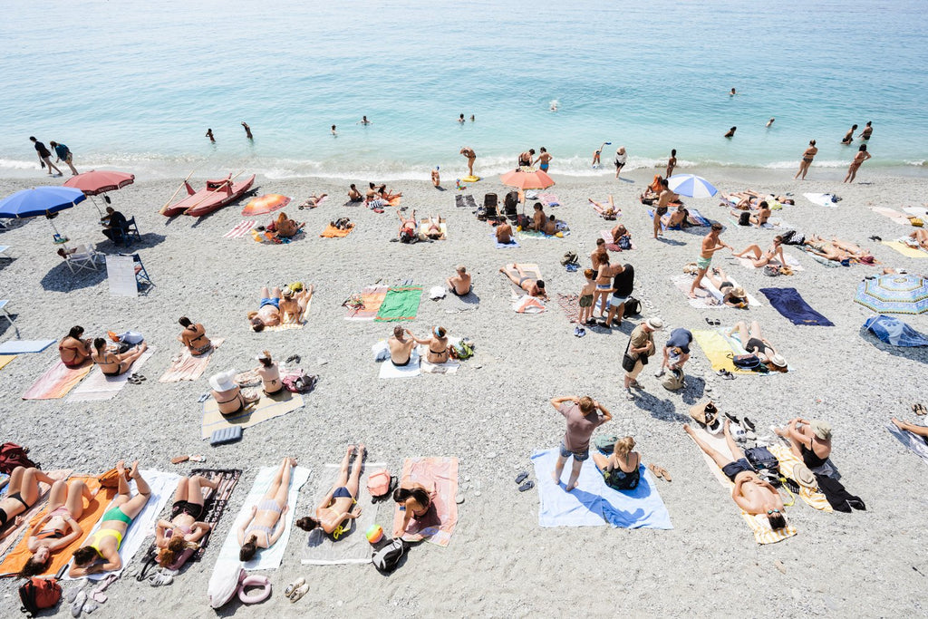 People lying on Monterosso beach with pebbles in Cinque Terre