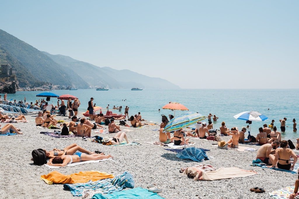 People lying on towels in the sun on Monterosso beach in Cinque Terre