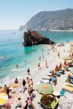 Big rock on Monterosso beach surrounded by people and blue water in Italy