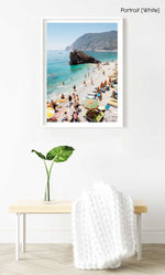 Big rock on Monterosso beach surrounded by people and blue water in Italy in a white fine art frame