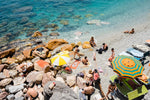 Umbrellas and people on beach with rocks and sand in Cinque Terre