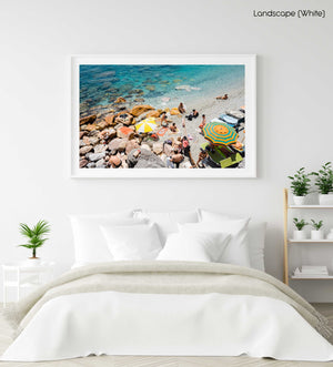 Umbrellas and people on beach with rocks and sand in Cinque Terre in a white fine art frame
