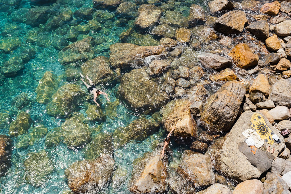 Two people swimming in clear blue water in Cinque Terre
