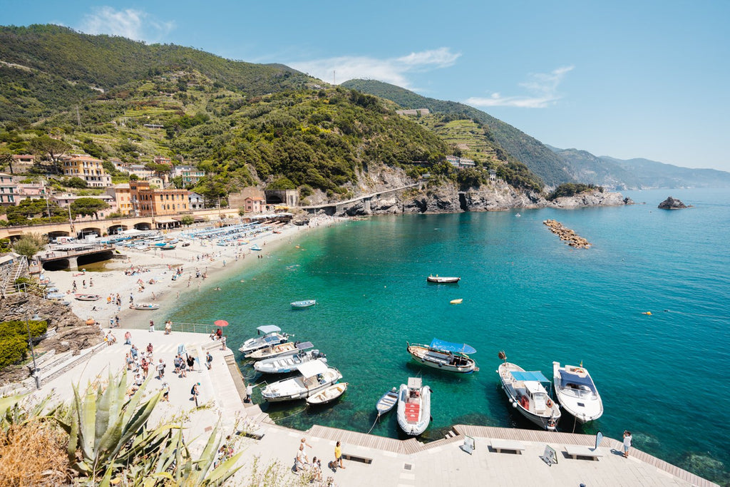 Boats docked along promenade of old town Monterosso during summer in Cinque Terre