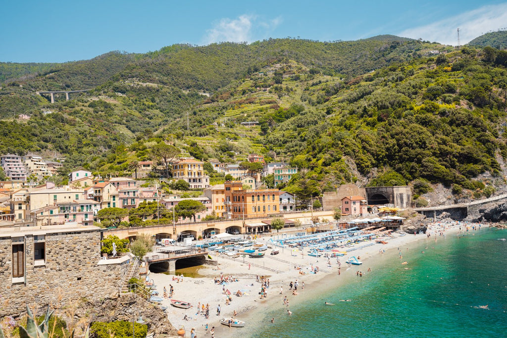 The old town of monterosso with people on beach and green hills