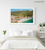 The old town of monterosso with people on beach and green hills in a white fine art frame