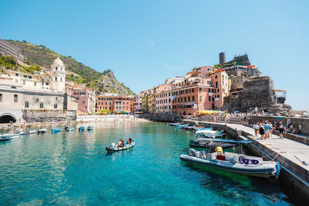 People on boat in blue water in colorful Vernazza of Cinque Terre