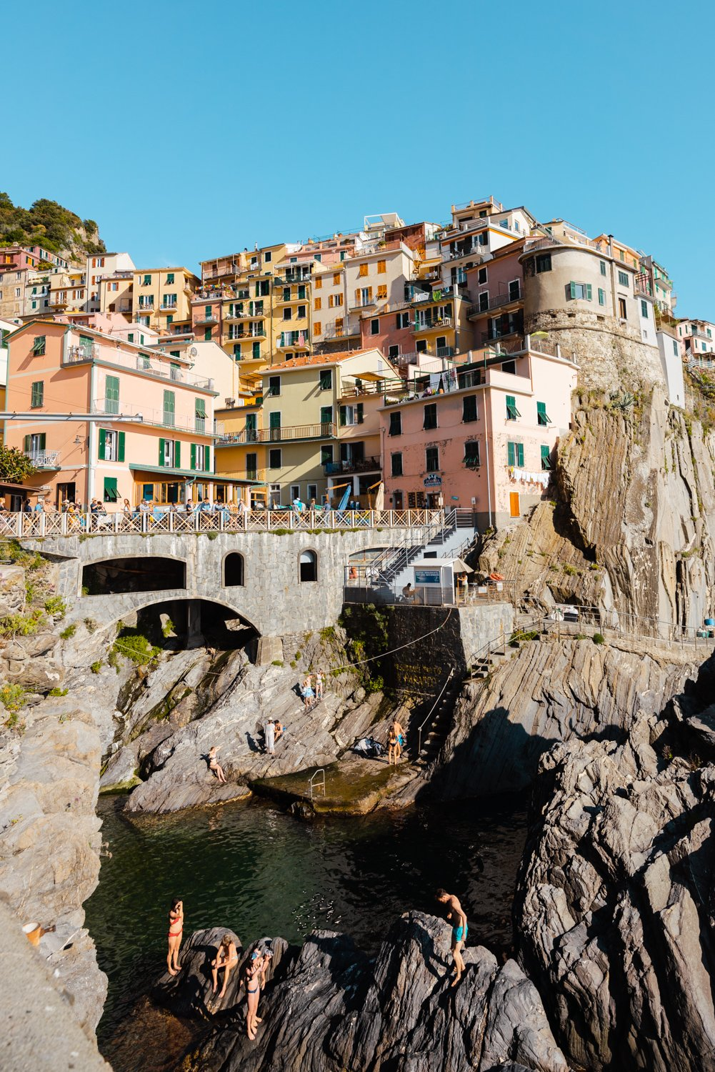 People swimming amongst bridge and colorful buildings of Manarola in Cinque Terre