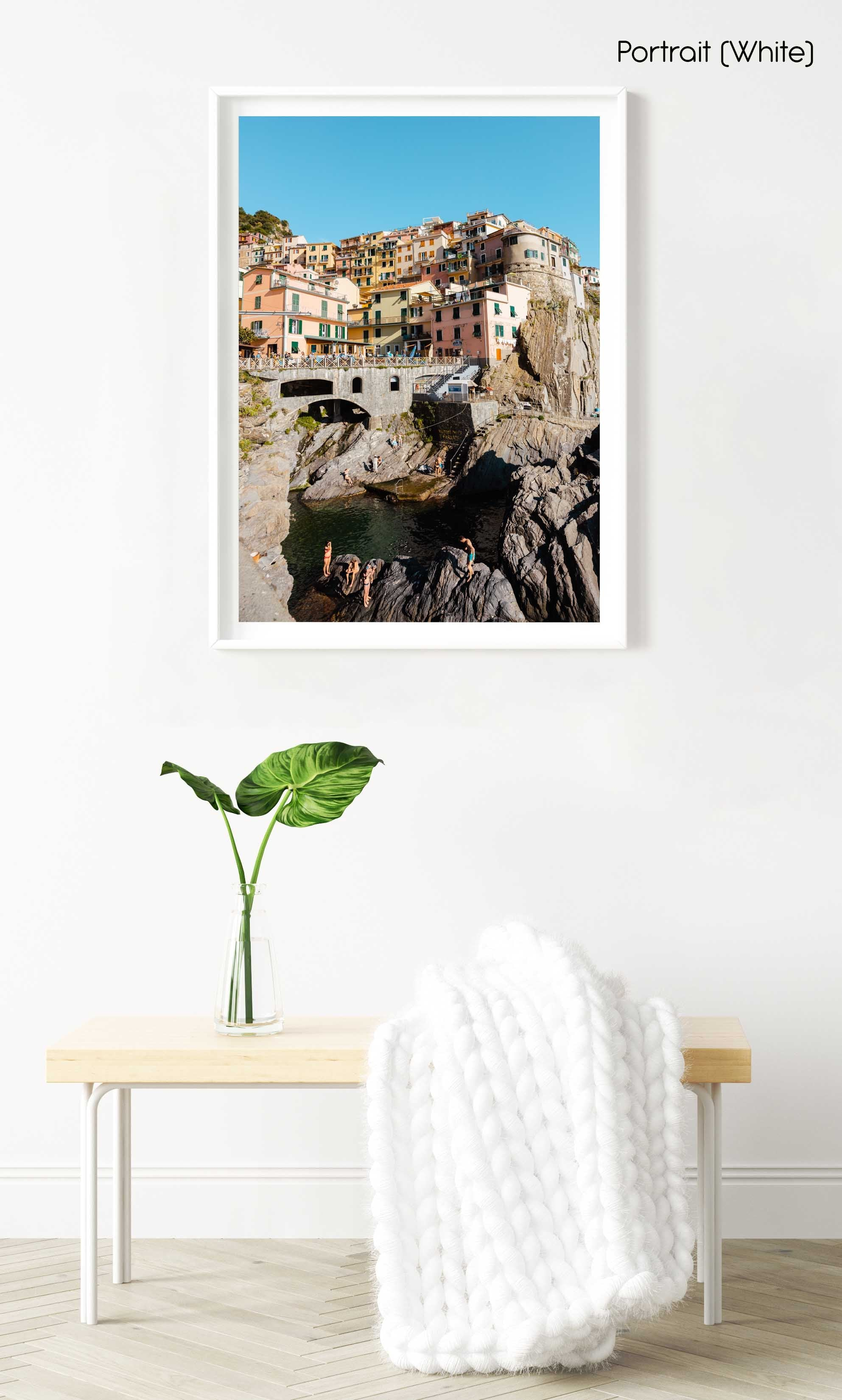 People swimming amongst bridge and colorful buildings of Manarola in Cinque Terre in a white fine art frame